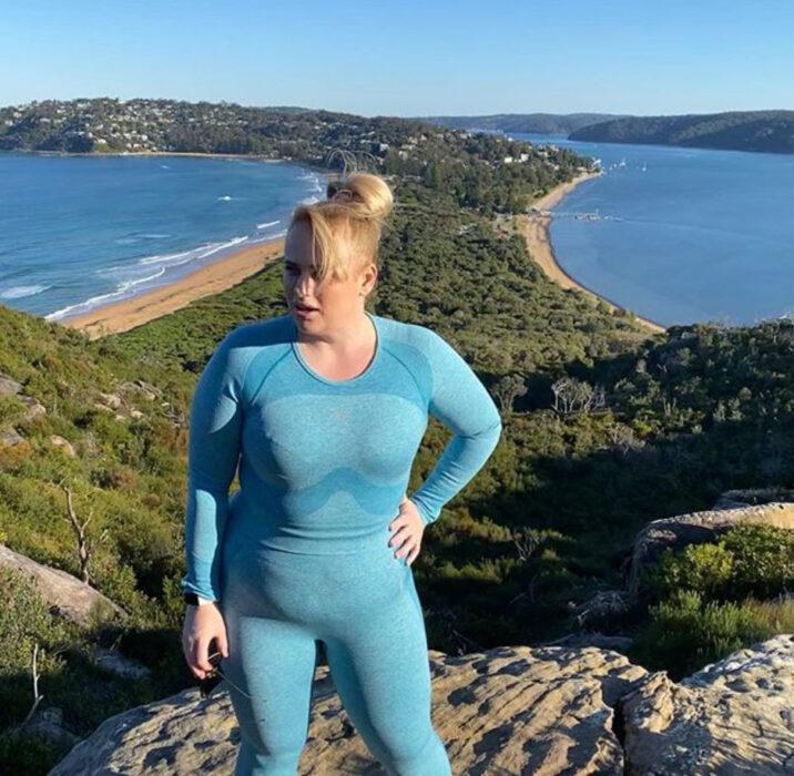 Rebel Wilson usando un conjunto deportivo color azul y posando después de haber hecho hicking