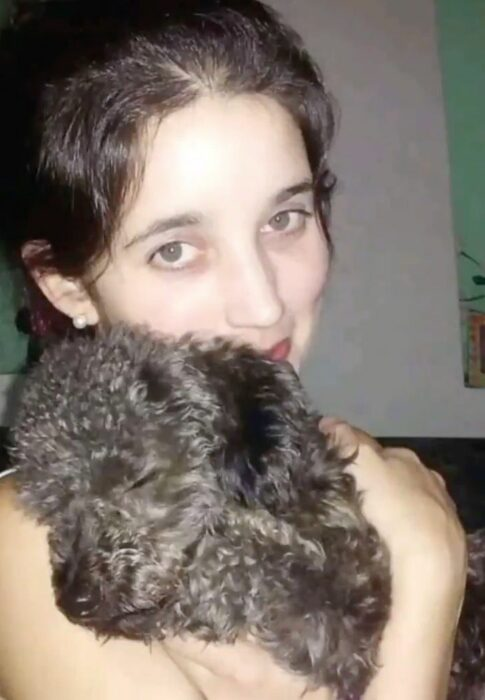 Johanna cargando a su perro Benito, un frenshpoodle negro, que se ha quedado dormido