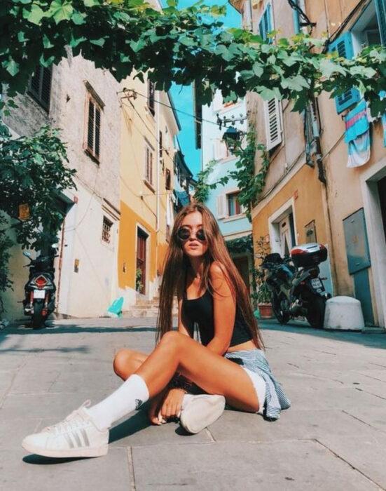 Chica sentada sobre el piso posando para una fotografía