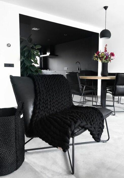 Sofá de color negro con una manta tejida igual de color negro