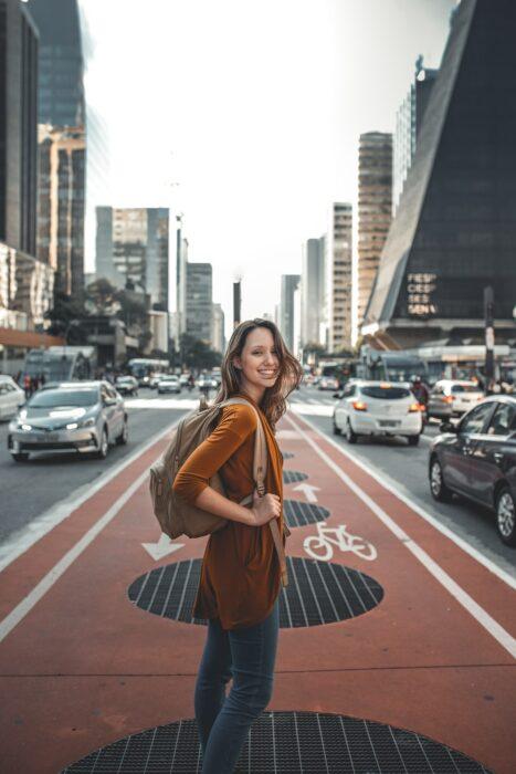Chica caminando por una ciclovía de la ciudad cargando una mochila en los hombros