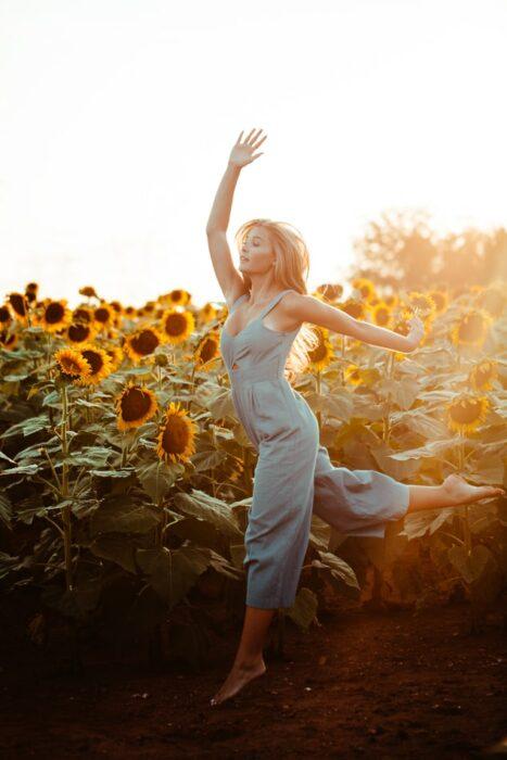 Chica bailando en un campo de girasoles gigantes