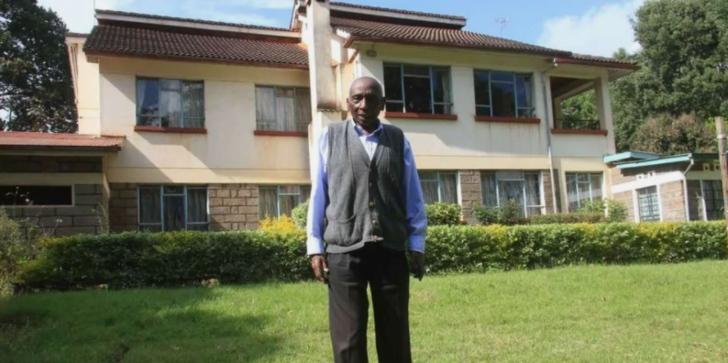 Nduhiu Njama y su mansión detrás de él
