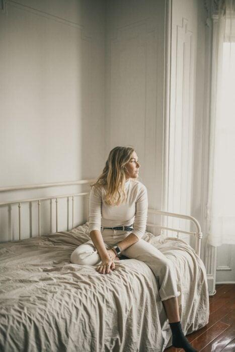 Chica sentada en la cama mirando a la ventana