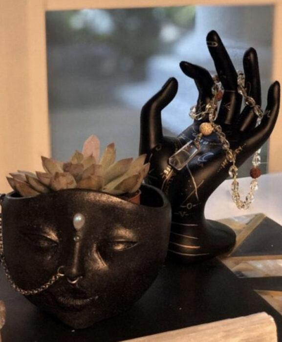 Macetita en forma de rostro y mano de joyero, ambos en color negro