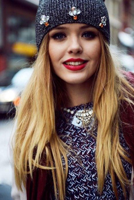 Chica llevando gorro tejido con aplicaciones de joyería de fantasía; ideas para llevar gorros y sombreros en otoño