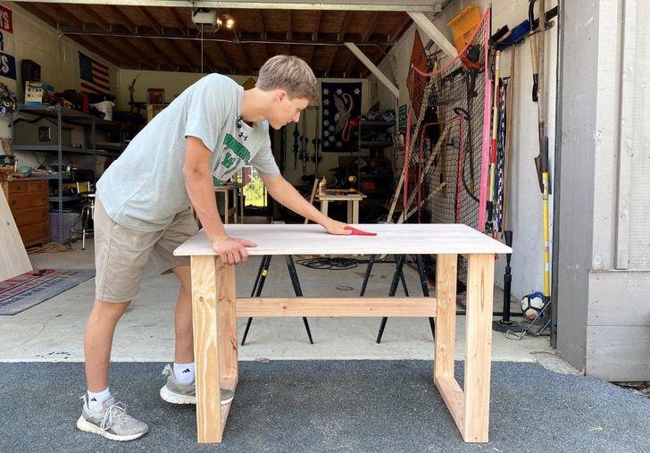 Colby Samide terminando de lijar un escritorio que el mismo construyó