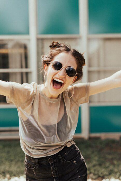 Chica con los brazos extendidos, usando gafas de sol y sonriendo