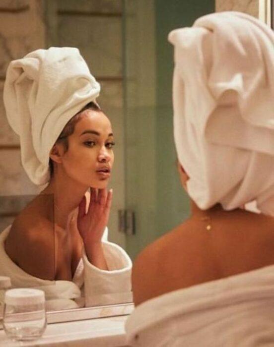 Chica saliendo de bañarse, mirándose en el espejo