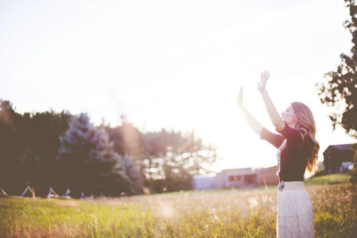 Chica extendiendo sus manos hacía el cielo