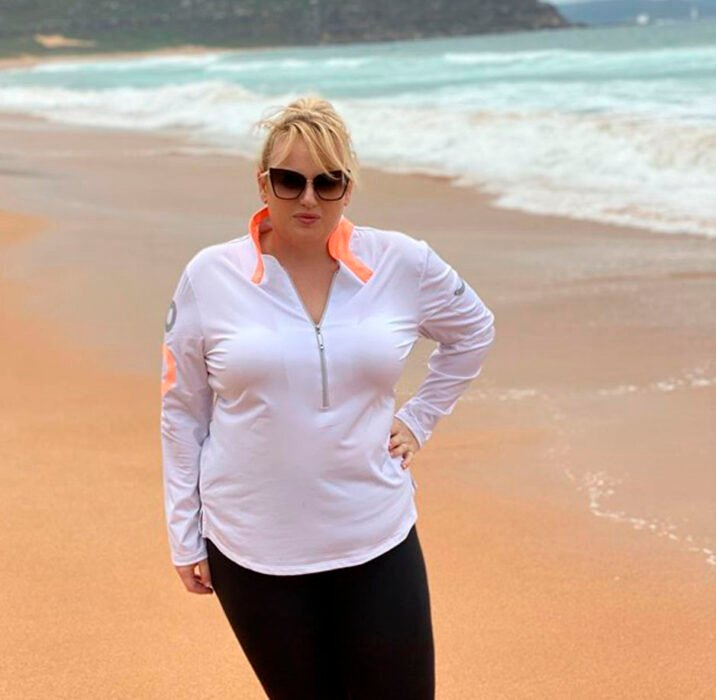 Rebel Wilson usando prendas deportivas y gafas de sol dando una caminata por la playa