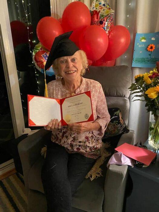 Eileen Delaney mostrando su diploma de egresada y usando un birrete