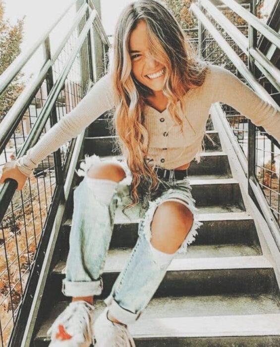 Chica sentada sobre unas escaleras