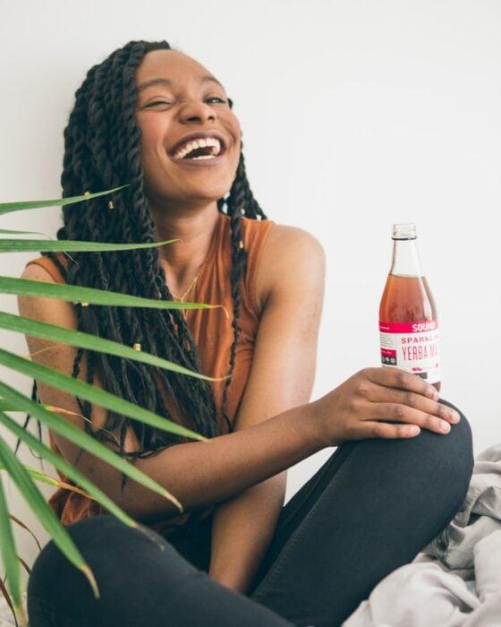 Chica de tez negra, con rastas sentada tomando un refresco y riéndo