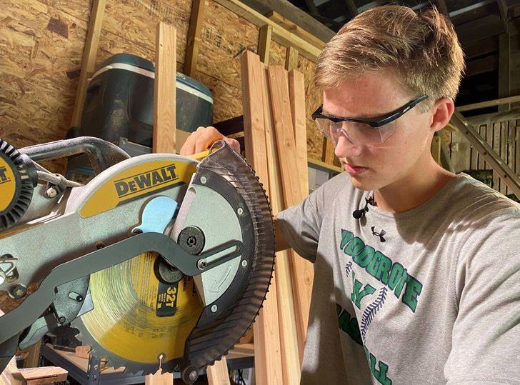 Colby Samide cortando madera para construir más escritorios