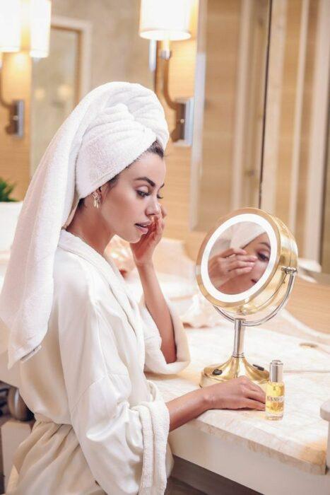 Chica saliendo de bañarse realizando su rutina facial