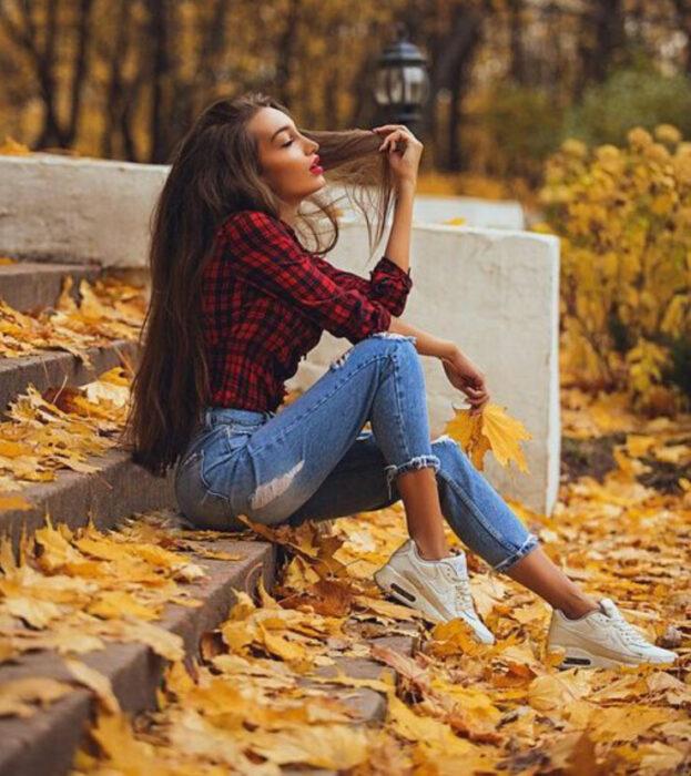Chica sentada en unas escaleras donde está lleno de hojas de otoño
