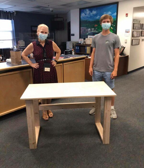 Colby Samide entregando un escritorio a una mujer