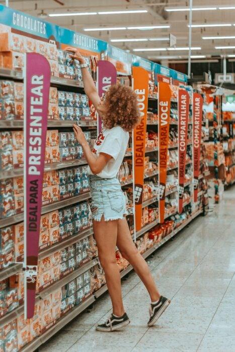 Chica en el supermercado realizando algunas compras