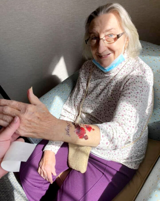 Abuelitos en asilo se hacen tatuajes temporales; flores en el brazo