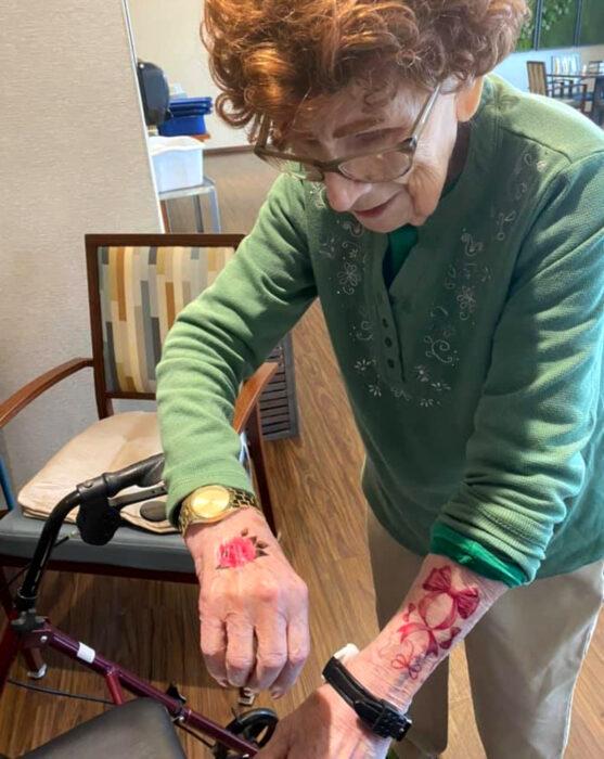 Abuelitos en asilo se hacen tatuajes temporales; flor y moño en las muñecas