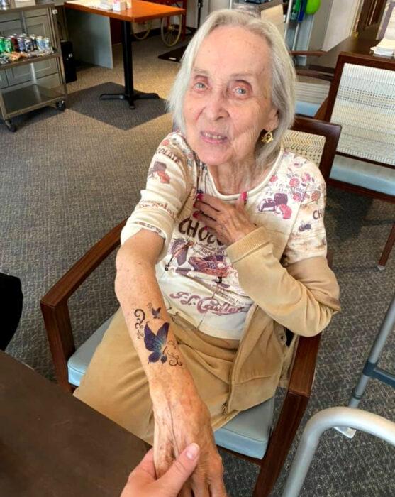 Abuelitos en asilo se hacen tatuajes temporales; mariposa en el brazo