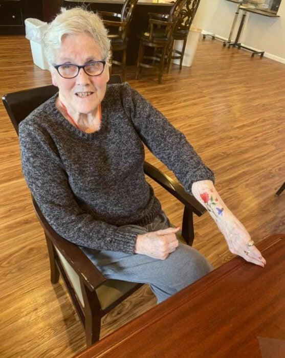 Abuelitos en asilo se hacen tatuajes temporales; flor con mariposa en la muñeca