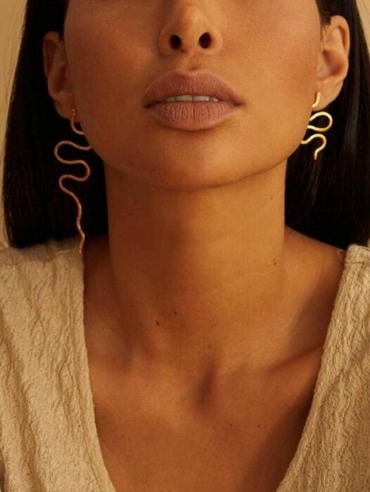 Girl wearing asymmetrical earrings in the shape of snakes