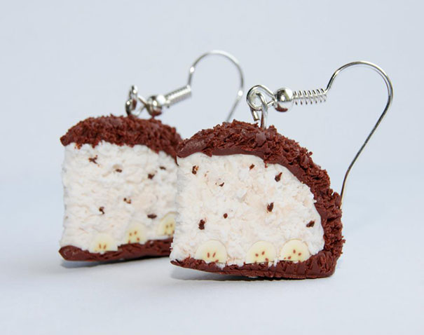 Small earrings in the shape of a slice of cake with cream