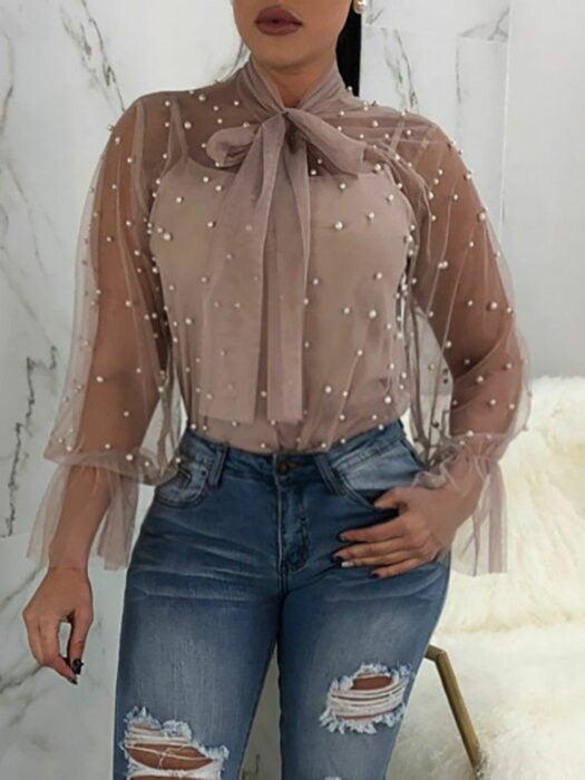 Chica con una blusa de color rosa con pequeñas perlas de color plateado