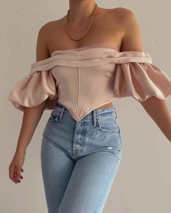 Chica con una blusa de color rosa estilo corsé