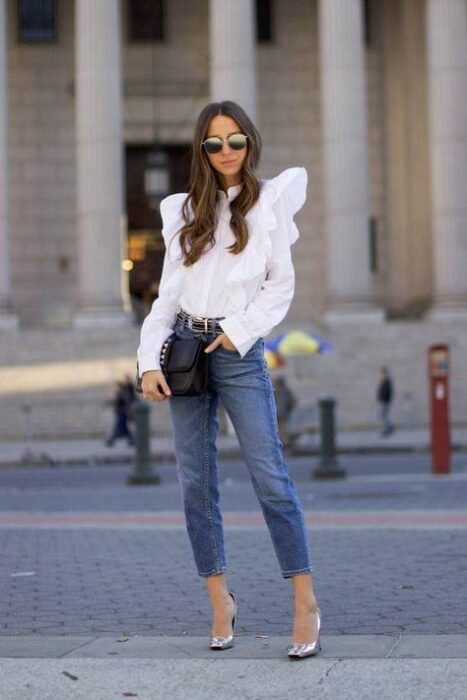 Girl in a white blouse with jeans and heels