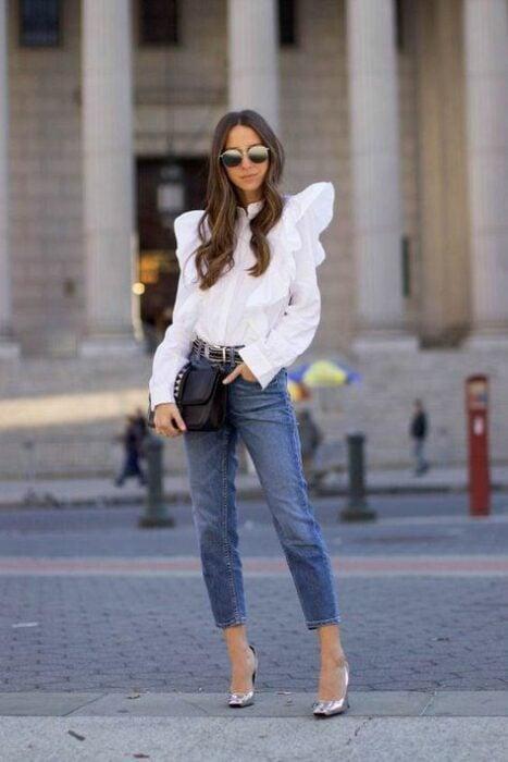 Chica con una blusa de color blanco con jeans y tacones
