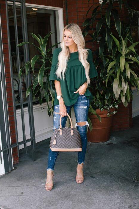 Chica con una blusa de color verde con jeans