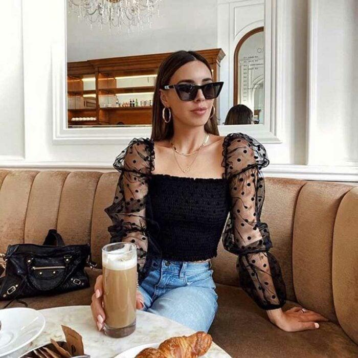 Chica con una blusa de color negro con transparencias en las mangas