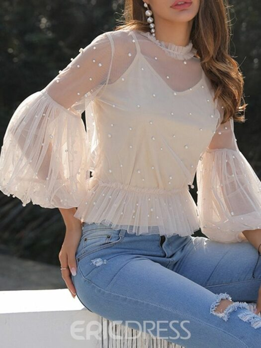 Girl wearing a cream colored blouse with details on