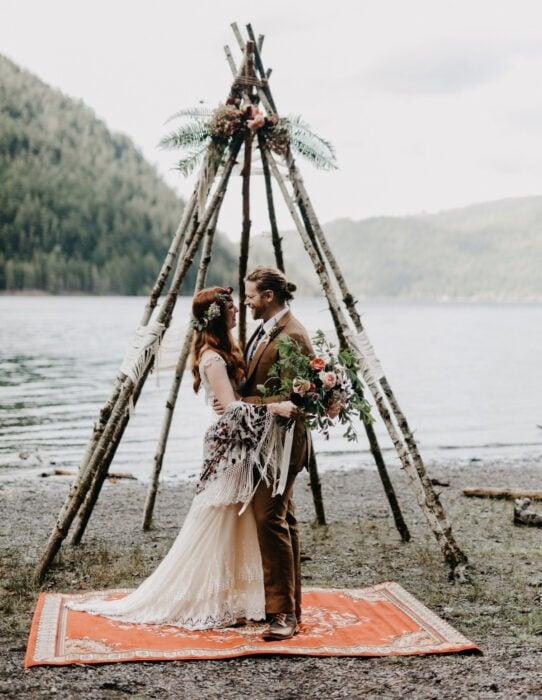 Ideas para una boda vikinga; pareja de novios a la orilla de lago en un altar de madera con flores