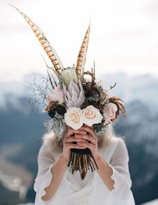 Ideas para una boda vikinga; ramo de flores y plumas