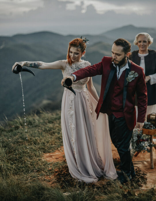 Ideas para una boda vikinga; novios con vasos de cuernos, vestido de encaje y saco rojo vino