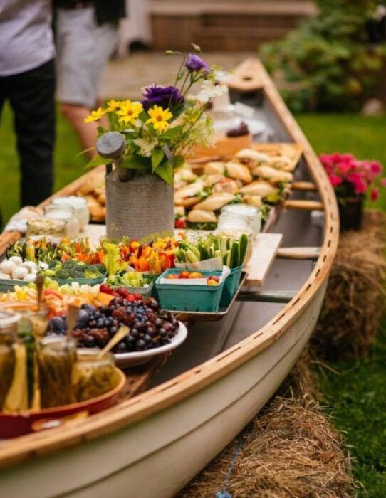 Ideas para una boda vikinga; mesa de dulces y bebidas hecha con canoa, balsa