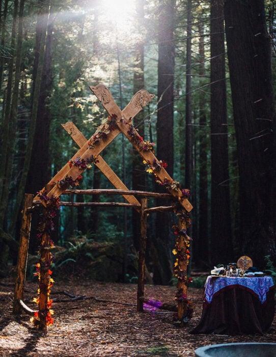 Ideas para una boda vikinga; altar de madera con flores en el bosque
