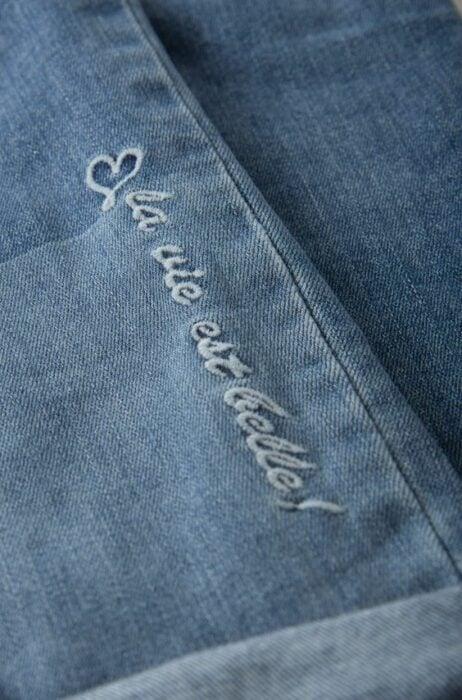 Bordado en jeans de una frase en hilo azul cielo