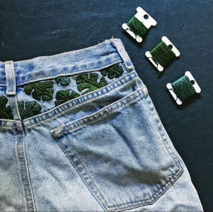 Green plant leaf embroidery on jeans