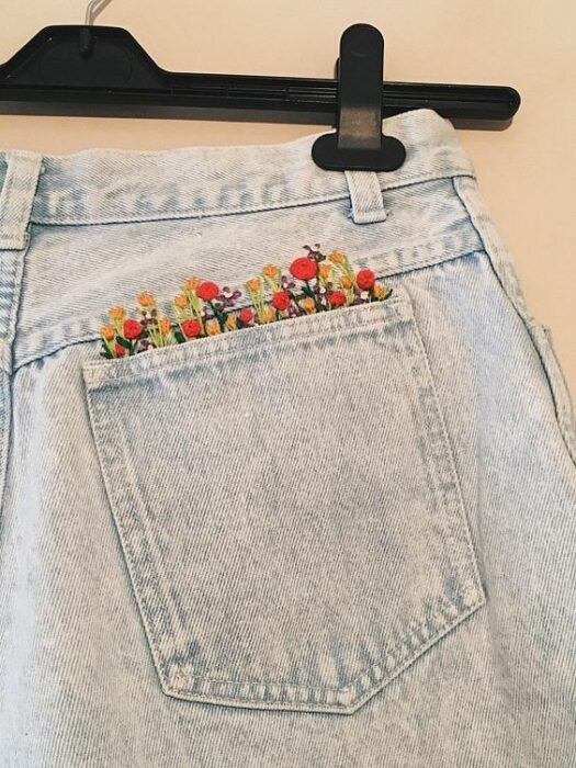 Embroidery on jeans of a field of flowers of different colors