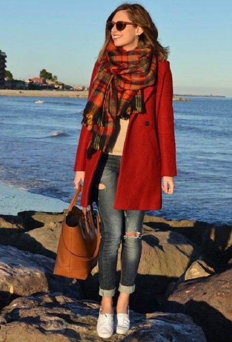 Chica usando bufanda larga de color roja con lineas grises y negras, jeans, y abrigo rojo
