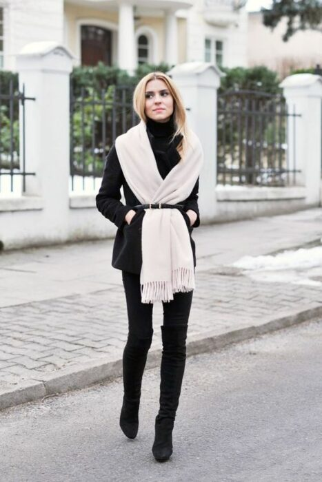 Girl wearing long beige scarf and black outfit and black belt