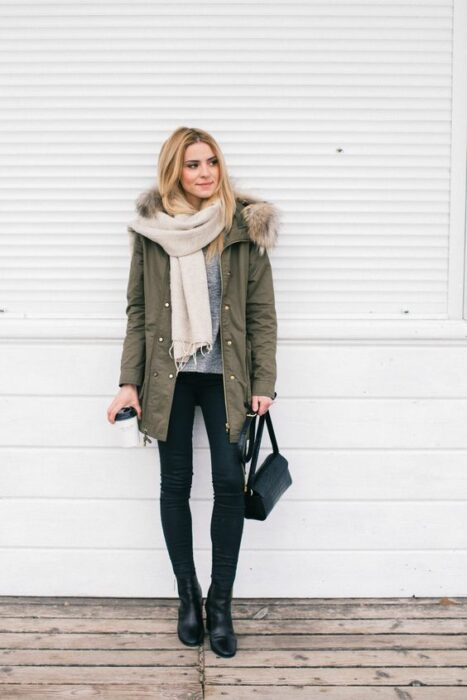 Girl wearing long beige scarf, military green camaharra, black jeans and ankle boots of the same color