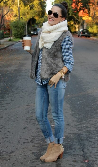 Girl wearing long beige scarf, button down shirt, furry vest, jeans and ankle boots