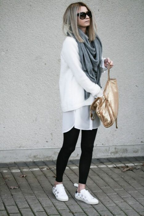 Girl wearing long gray scarf, with white baggy sweater and black leggings