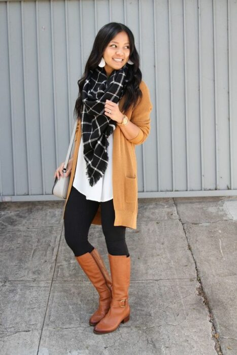 Girl wearing long black scarf with white squares, with white blouse, long mustard sweater, black leggings and camel high boots